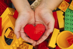 Lego red heart in child hands Royalty Free Stock Image