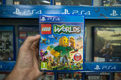 Lego Worlds. Bratislava, Slovakia, circa april 2017: Man holding Lego Worlds videogame on Sony Playstation 4 console in store Royalty Free Stock Image