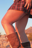 Legs. Image of woman's tanned legs in a pleated skirt against a desert background Stock Images