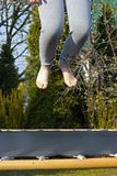 Jump over the trampoline. Legs above the trampoline during jumping, in the background, a visible spring garden royalty free stock photos