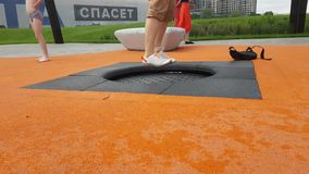 Legs Of adult woman Jumping On A small Trampoline. JUL 22, 2018 MOSCOW, RUSSIA: Legs Of adult woman Jumping On A small Trampoline outdoors in new modern public stock video footage
