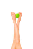 Legs and apple. Female legs keeping  green apple isolated on white Royalty Free Stock Photography