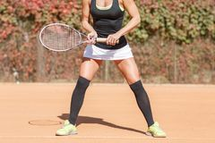 Legs of an athlete girl near a tennis racket Royalty Free Stock Photos