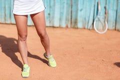 Legs of an athlete girl near a tennis racket Stock Photos