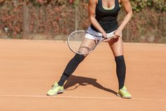 Legs of an athlete girl near a tennis racket Royalty Free Stock Image