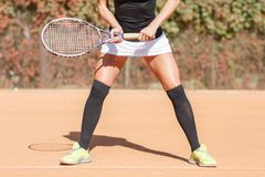 Legs of an athlete girl near a tennis racket Royalty Free Stock Photo