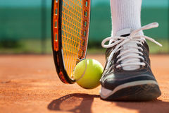 Legs of athlete near the tennis racket and ball. Legs of sportive man  near the tennis racquet and balls Royalty Free Stock Images