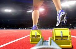Legs of athlete on running block in the stadium Royalty Free Stock Photos