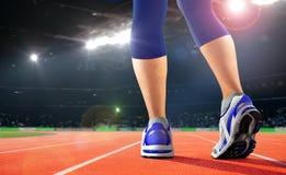 Legs of athlete on running track in the stadium Stock Photo