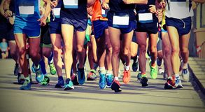 Legs of athletes running the marathon on the city with old vint. Athletes running the marathon on the city street with old vintage effect royalty free stock photos