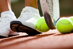 Legs of athletic girl near the tennis racket. And balls Stock Photography