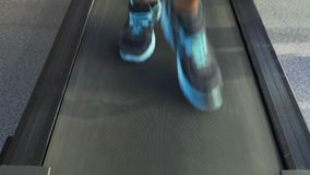 Legs of athletic male running on treadmill, cardio workout in the fitness club. Stock footage stock footage