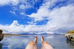 The legs of an athletic man in natural thermal hot spring Polloquere, Salar De Surire salt lake, Isluga Volcano National. Park, Chile, South America Royalty Free Stock Photography