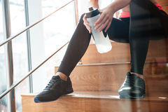 Legs of attractive woman athlete sitting on stairs in gym. Beautiful slim legs of attractive woman athlete sitting on stairs in gym with bottle of water stock photos