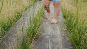 The legs of the baby make the first unsteady steps along the wooden path among the grass. First successes of children
