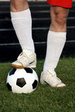 Legs and ball. Legs of soccer player with classic soccer ball over green grass royalty free stock photography