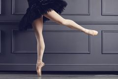 Legs of a ballerina on a black background. The concept of ballet dancing stock image