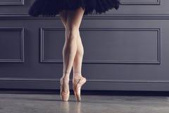 Legs of a ballerina on a black background. The concept of ballet dancing stock photos