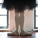 Legs of a ballerina closeup. The legs of a ballerina in old pointe. Rehearsal ballerina in the hall. Contour light from the window royalty free stock image