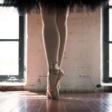 Legs of a ballerina closeup. The legs of a ballerina in old pointe. Rehearsal ballerina in the hall. Contour light from the window royalty free stock photo