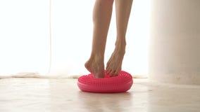 Legs of ballerina on massage hemisphere. Slim legs of ballerina close up. Training balance and accuracy dance step. Girl stands barefoot on massage hemisphere stock footage