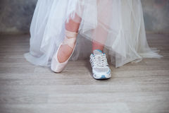 Legs of a ballerina, one foot shod in sneakers other in pointe shoes Stock Image