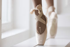 Legs of a ballerina in pointe near the window. Legs of a ballerina in pink pointe shoes with a bow are dancing near the window Royalty Free Stock Photo