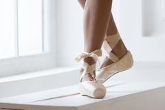 Legs of a ballerina in pointe. Legs of a ballerina in pink pointe shoes with a bow are dancing near the window Stock Photos