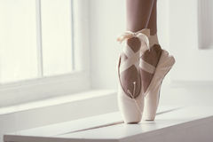 Legs of a ballerina in pointe. Legs of a ballerina in pink pointe shoes with a bow are dancing near the window Royalty Free Stock Photo