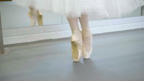 The legs of ballerina in pointe stand on releve in the fifth poition and turn left and right.  stock video footage