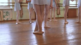 Legs of ballerinas in blue suits standing on floor and walk away during ballet class. Legs of ballerinas in blue suits standing on floor and walk away during stock video footage