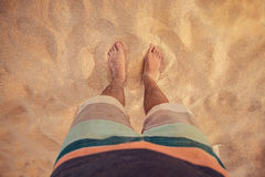 Legs Barefoot On The Beach. Lower body of a man standing on a sandy beach in surfer shorts Stock Photo