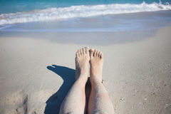 Legs on the beach, female feet in  sand Stock Photo