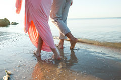 Legs on beach. Foot spa. A young loving couple hugging and kissing on the beach at sunset. Two lovers, man and woman barefoot near the water. Summer in love royalty free stock image