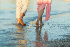 Couple on the beach. Legs on beach. Foot spa. Two lovers, man and woman barefoot near the water. Summer in love Stock Photography