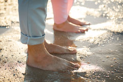 Couple on the beach. Legs on beach. Foot spa. Two lovers, man and woman barefoot near the water. Summer in love Stock Image