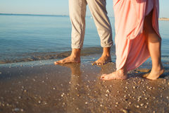 Couple on the beach. Legs on beach. Foot spa. Two lovers, man and woman barefoot near the water. Summer in love Royalty Free Stock Photo