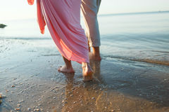Couple on the beach. Legs on beach. Foot spa. Two lovers, man and woman barefoot near the water. Summer in love Royalty Free Stock Images