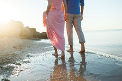 Couple on the beach. Legs on beach. Foot spa. Two lovers, man and woman barefoot near the water. Summer in love Stock Photo