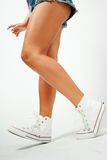 Legs of a beautiful girl in sneakers Royalty Free Stock Images