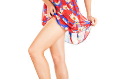 Legs of beautiful model covered with short pretty skirt. Stock Photos