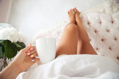 The legs of a beautiful young woman as she lies in bed. Soft photo of woman with cup of coffee in hand and legs raised up high lying on bed in bedroom Stock Photo