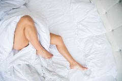 Legs on the bed in white bedclothes Stock Image