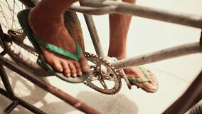 The legs of a beggar on the pedals of a bicycle while riding. Close-up. Manila. Philippines. The legs of a beggar on the pedals of a bicycle while riding. Close stock video footage