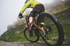 Legs of bicyclist and rear wheel close-up view of back mtb bike in mountains against background of rocks in foggy. Weather. The concept of extreme sports stock images