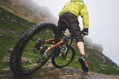 Legs of bicyclist and rear wheel close-up view of back mtb bike in mountains against background of rocks in foggy royalty free stock image