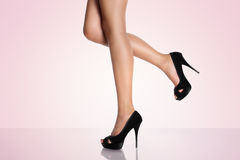 Legs with black high-heeled shoes on a pink background. Isolated Stock Photography