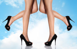 Legs with black high-heeled shoes on a sky background. With clouds Stock Photography