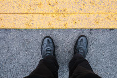 Legs with black shoes on the blacktop Stock Photos