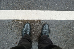 Legs with black shoes on wet ground Royalty Free Stock Images
